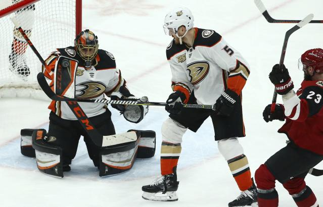 Anaheim Ducks goaltender Ryan Miller, left, gets some help from Ducks defenseman Korbinian Holzer, center, on a shot from Arizona Coyotes defenseman Oliver Ekman-Larsson, right, during the second period of an NHL hockey game Tuesday, March 5, 2019, in Glendale, Ariz. (AP Photo/Ross D. Franklin)