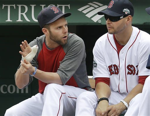 Boston Red Sox's Dustin Pedroia gestures with his bandaged hand as he chats with Cody Ross, right, during the first baseball game of a day-night doubleheader against the New York Yankees at Fenway Park in Boston, Saturday, July 7, 2012. Pedroia is on the 15-day disabled list (retroactive to July 4) with a right thumb sprain. (AP Photo/Elise Amendola)
