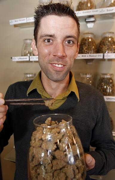 "This Thursday, April 11, 2013, photo shows Matt Brown, co-owner of Denver'S new ""My 420 Tours, shows a sampling of marijuana at a dispensary in Denver. ""My 420 Tours,"" gives traveling pot users everything but the drug. Brown has sold 160 tour packages to visiting pot smokers for the April 20 weekend. Prices start at $499, not including hotel or air. Instead, the service plans to pick up marijuana tourists at the airport in limousines, escort them to Cannabis Cup and other Denver-area marijuana celebrations and take them to a cannabis-friendly hotel (a national chain that has given permission for Denver patrons to smoke marijuana on outdoor patios but doesn't want its name advertised). (AP Photo/Ed Andrieski)"