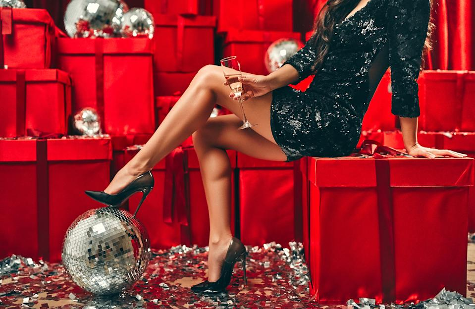 Party concept. Sexy legs of woman in glamour style shoes with silver luxury confetti on the floor. New Year and Christmas holidays. Against the background of red gift boxes and disco balls.