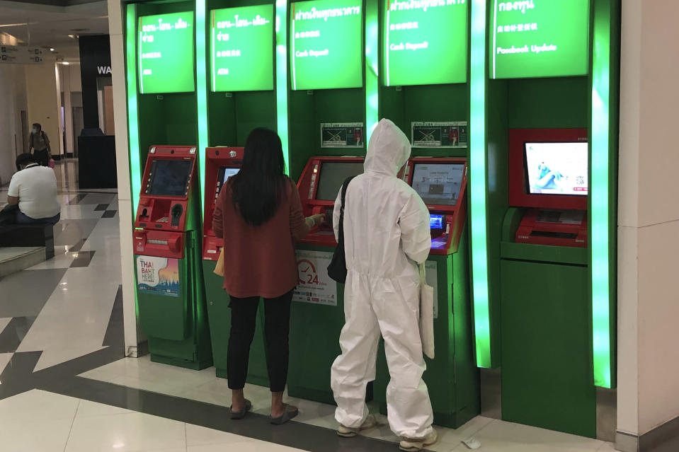 A person wearing full protective gear uses an ATM outside a bank Bangkok, Thailand, Wednesday, July 21, 2021. (AP Photo/Grant Peck)