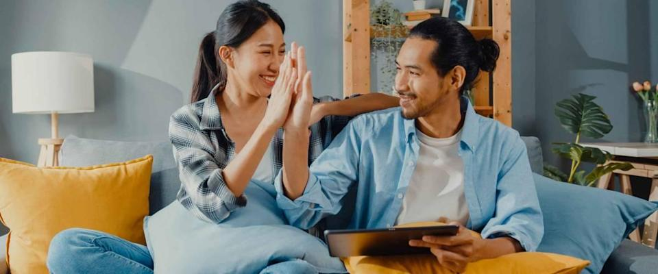 Happy asian young attractive couple man and woman sit on couch use tablet to find a low mortgage rate.