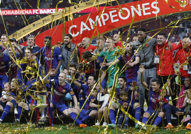 Barcelona team players pose with the trophy after the Copa del Rey final soccer match between Barcelona and Sevilla at the Wanda Metropolitano stadium in Madrid, Spain, Saturday, April 21, 2018. (AP Photo/Paul White)