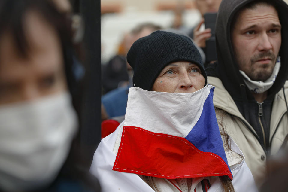 A woman wears a Czech flag as a mask as demonstrators gather to protest the COVID-19 preventative measures downtown Prague, Czech Republic, Wednesday, Oct. 28, 2020. Coronavirus infections in the Czech Republic have again jumped to record levels amid new restrictive measures imposed by the government to curb the spread. (AP Photo/Petr David Josek)