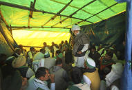 Indian farmers hold a meeting as they block a highway in protest against new farm laws at the Delhi-Uttar Pradesh state border, on the outskirts of New Delhi, India, Wednesday, Dec. 30, 2020. Protesting farmers fear the government will stop buying grain at minimum guaranteed prices and corporations will then push down prices. The government says the three laws approved by Parliament in September will enable farmers to market their produce and boost production through private investment. (AP Photo/Manish Swarup)