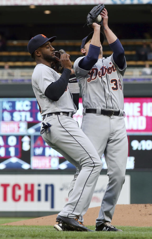 Detroit Tigers third baseman Niko Goodrum, left, backs off as pitcher Blaine Hardy catches a pop-up off the bat of Minnesota Twins' Max Kepler in the first inning of a baseball game Monday, May 21, 2018, in Minneapolis. (AP Photo/Jim Mone)