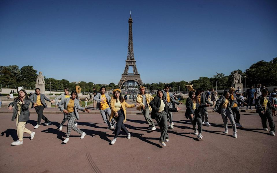 Dancers from Shee'z's group perform in front of the Eiffel Tower, Paris - AFP