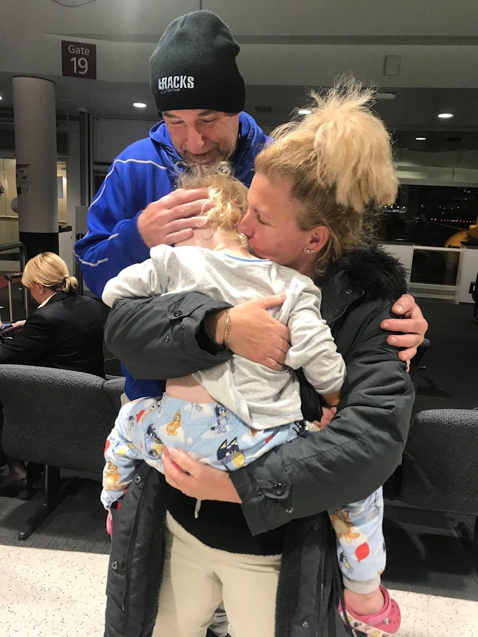 Then-3-year-old Poppy Wells gets a hug from her grandparents, Ian and Peggy McElligott, at the airport in July 2020.
