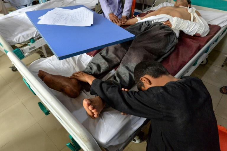A wounded man receives treatment at a hospital after a blast as his son touches his feet in Jalalabad on September 28, 2019 (AFP Photo/NOORULLAH SHIRZADA)
