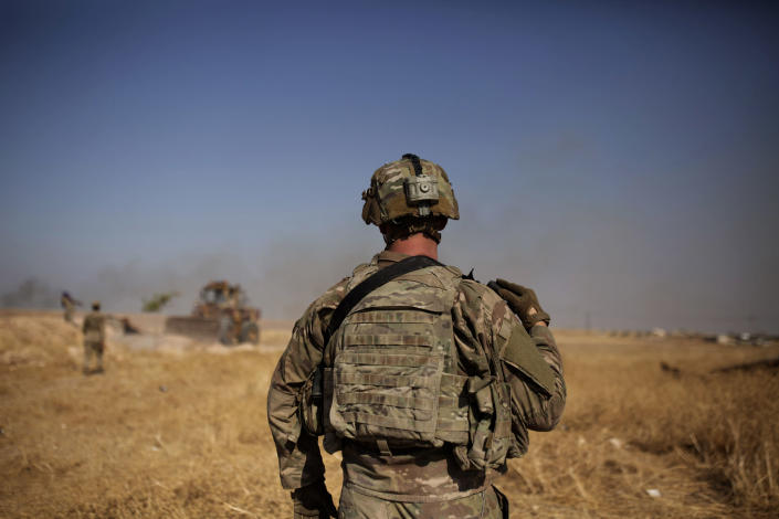 A U.S. special forces soldier watches Syrian Kurdish soldiers dismantle a fortification in the so-called