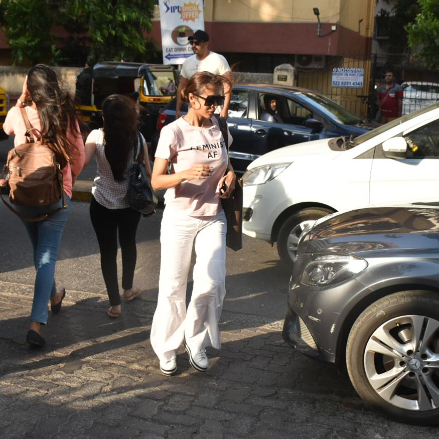 Malaika Arora wore a pink t-shirt with 'Feminist AF' written on it. She paired it with white trousers. (Image: Viral Bhayani)