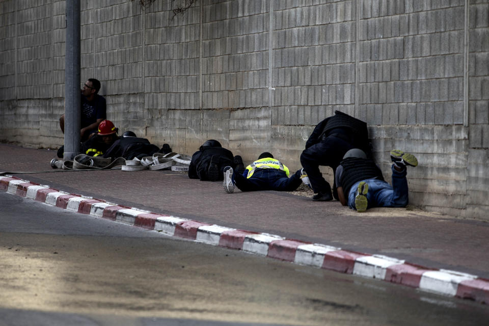 People take cover during an air-raid warning siren in Sderot, southern Israel , Israel, Tuesday, Nov. 12m 2019. Israel has killed a senior Islamic Jihad commander in Gaza in a rare targeted killing that threatened to unleash a fierce round of cross-border violence with Palestinian militants. (AP Photo/Tsafrir Abayov)