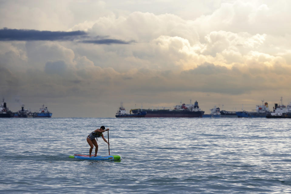 A stand up paddleboarder paddles past commercial vessels anchored at East Coast Park in Singapore.