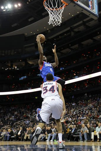 Philadelphia 76ers small forward Dorell Wright (4) shoots over Atlanta Hawks point guard Devin Harris (34) in first-half action of an NBA basketball game on Wednesday, March. 6, 2013, in Atlanta. (AP Photo/Todd Kirkland)