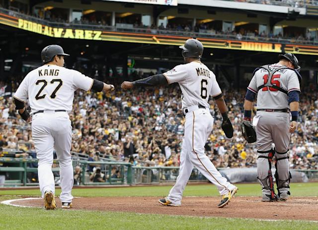 Pittsburgh Pirates' Jung Ho Kang (27) and Starling Marte (6) greet each other at home plate after scoring on a double by Pedro Alvarez as Atlanta Braves catcher A.J. Pierzynski (15) walks away in the first inning of a baseball game, Saturday, June 27, 2015, in Pittsburgh. (AP Photo/Keith Srakocic)