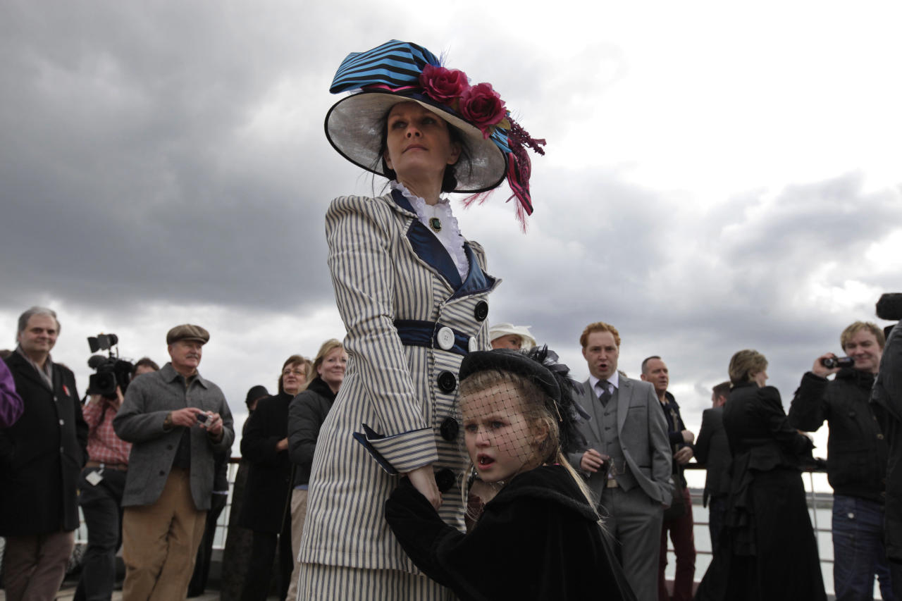 In this photo taken Sunday, April 8, 2012, wearing period costumes, British passenger Jacki Free holds her daughter, name not given, as the MS Balmoral Titanic memorial cruise ship sails from Southampton, England. A cruise carrying relatives of some of the more than 1,500 people who died aboard the Titanic nearly 100 years ago set sail from England on Sunday to retrace the ship's voyage, including a visit to the location where it sank. (AP Photo/Lefteris Pitarakis)