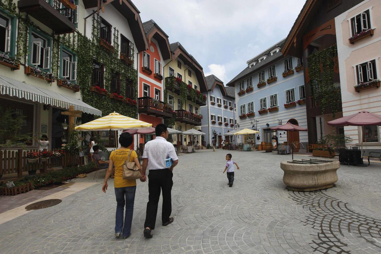 A family walks in the Chinese replica of Austria's UNESCO heritage site, Hallstatt village, in China's southern city of Huizhou in Guangdong province June 1, 2012. Metals and mining company China Minmetals Corporation spent $940 million to build this controversial site and hopes to attract both tourists and property investors alike, according to local newspaper reports. REUTERS/Tyrone Siu (CHINA - Tags: BUSINESS SOCIETY TRAVEL)