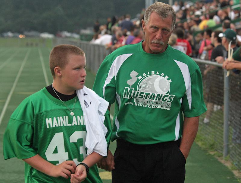Mainland Regional High School head football coach Bob Coffey, right, walks with his son during a memorial vigil for four members of the football team who were killed Saturday in a crash on the Garden State Parkway, Sunday, Aug. 21, 2011 in Linwood, N.J.  (AP Photo/Sean Fitzgerald)