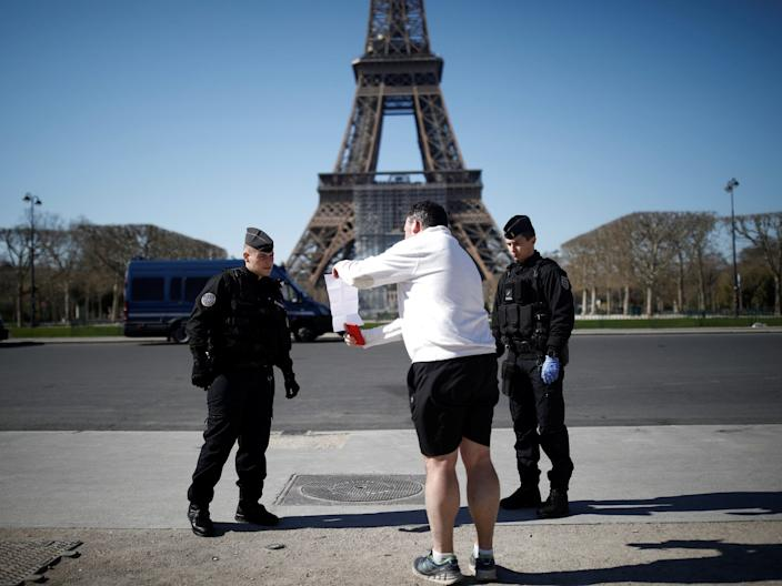 French Gendarmes confront a man near the Eiffel Tower in Paris during lockdown, March 23, 2020.