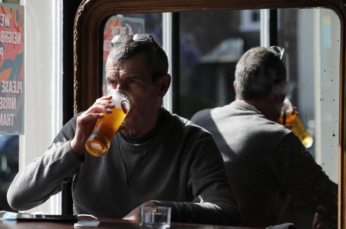 A man drinks a pint of beer in the Black Lion pub in Hammersmith in London, Monday, May 17, 2021. Drinks were raised in toasts and reunited friends hugged each other as thousands of U.K. pubs and restaurants opened Monday for indoor service for the first time since early January. Yet the prime minister sounded a cautious tone, warning about a more contagious COVID-19 variant first discovered in India that threatens reopening plans. (AP Photo/Frank Augstein)