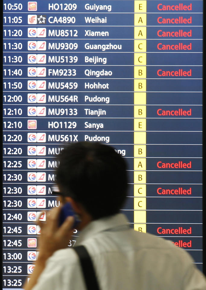 A man talks on his mobile phone next to a flight schedule information board which shows many flights are canceled in red characters due to Typhoon Muifa at Honqiao Airport in Shanghai, China, Sunday, Aug. 7, 2011. Typhoon Muifa is forecast to hit China early Monday morning, making landfall in the eastern province of Shandong and skimming the coast as it heads north, China's Central Meteorological Administration said. (AP Photo/Eugene Hoshiko)