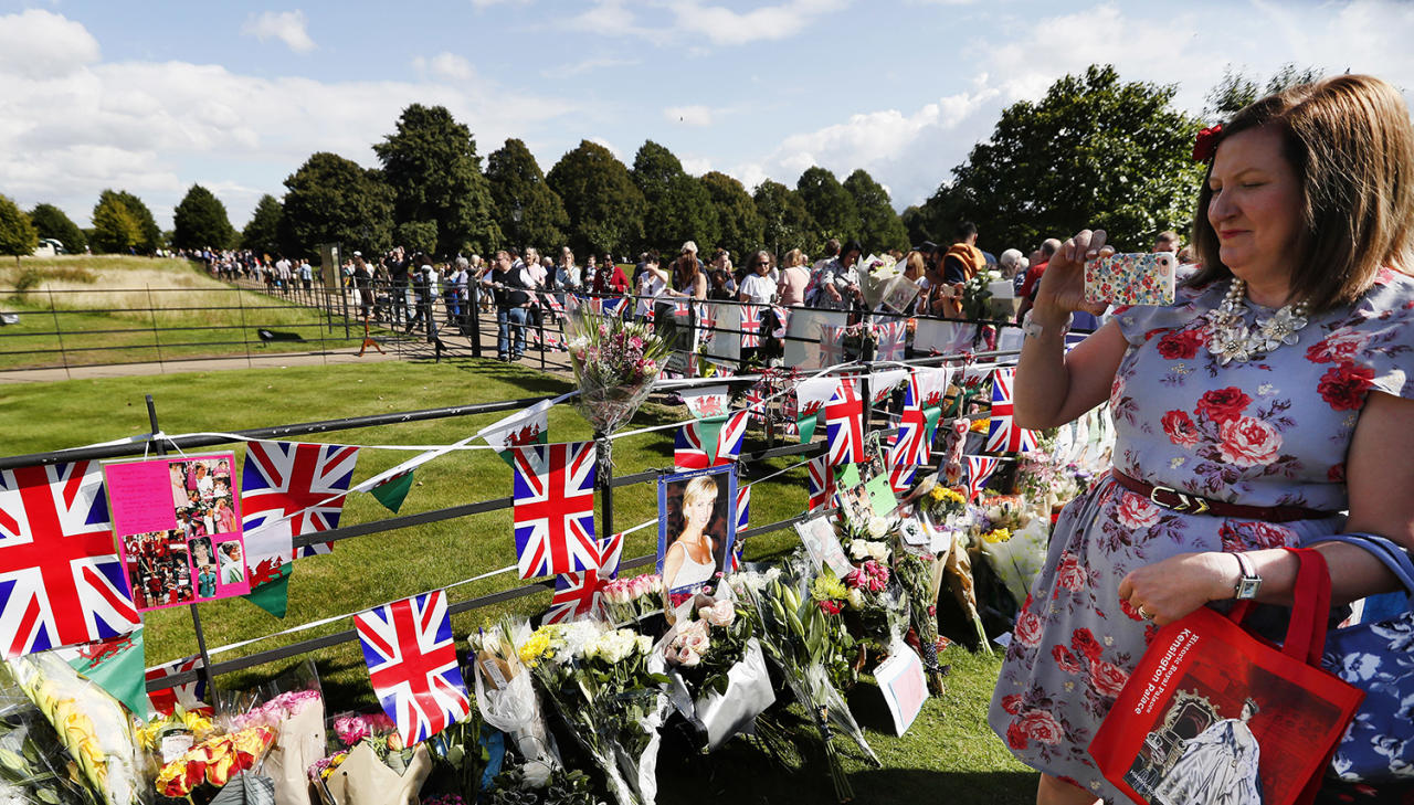 <p>A woman takes a photograph as people crowd around the gates of Kensington Palace in London to pay tribute to the late Diana, Princess of Wales, Aug. 31, 2017. (Photo: Kirsty Wigglesworth/AP) </p>