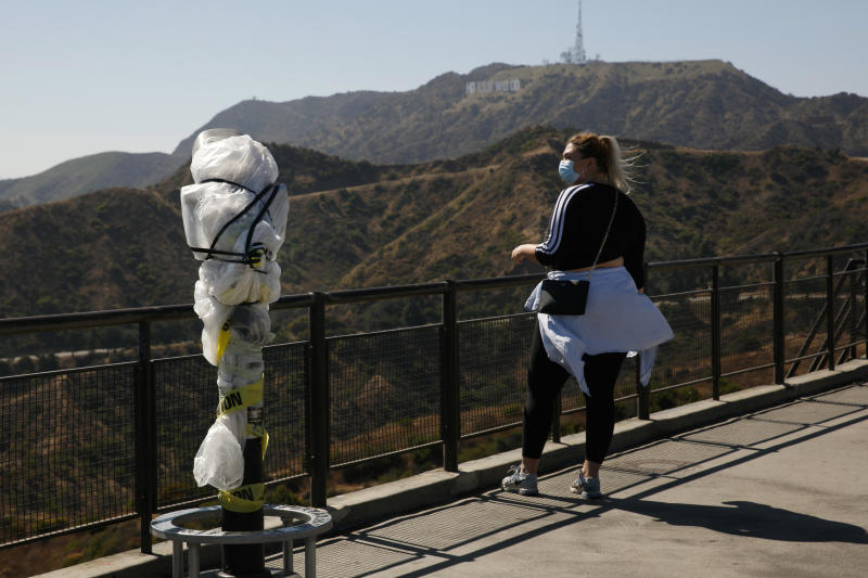 """A woman with a face mask stands next to a telescope wrapped in plastic to prevent the spread of COVID-19 at the Griffith Observatory overlooking downtown Los Angeles, Wednesday, July 15, 2020. Coronavirus cases have surged to record levels in the Los Angeles area, putting the nation's largest county in """"an alarming and dangerous phase"""" that if not reversed could overwhelm intensive care units and usher in more sweeping closures, health officials said Wednesday. (AP Photo/Jae C. Hong)"""