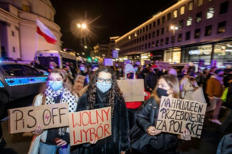 Protesters in Warsaw hold anti-government signs at the mass protest against a court ruling banning almost all abortions in Poland