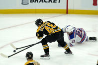 Boston Bruins defenseman Matt Grzelcyk (48) and New York Rangers defenseman Anthony Bitetto (22) chase the puck in the first period of an NHL hockey game, Thursday, May 6, 2021, in Boston. (AP Photo/Elise Amendola)