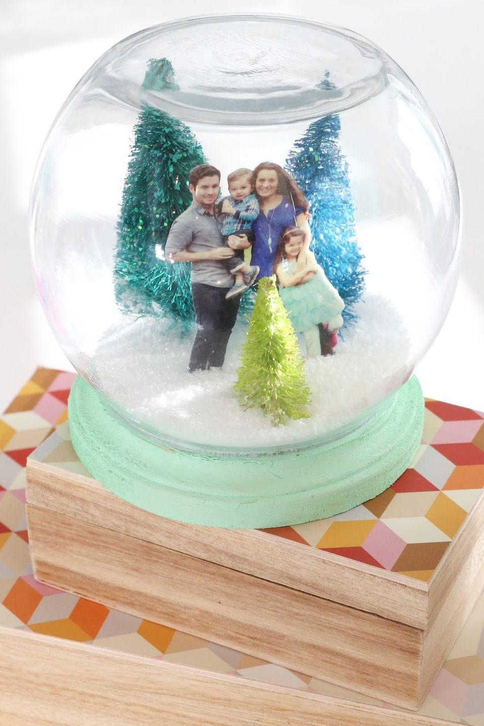 """<p>The only thing we love more than a pretty snow globe is a pretty <em>personalized</em> snow globe. Customize yours with a family portrait and colorful bottle brush trees. </p><p><strong>Get the tutorial <a href=""""https://akailochiclife.com/2015/12/craft-it-family-portrait-snow-globe.html"""" rel=""""nofollow noopener"""" target=""""_blank"""" data-ylk=""""slk:A Kailo Chic Life"""" class=""""link rapid-noclick-resp"""">A Kailo Chic Life</a>.</strong></p><p><strong><a class=""""link rapid-noclick-resp"""" href=""""https://www.amazon.com/KUUQA-Plastic-Ornaments-Tabletop-Decoration/dp/B077D43FZC/?tag=syn-yahoo-20&ascsubtag=%5Bartid%7C10050.g.23489557%5Bsrc%7Cyahoo-us"""" rel=""""nofollow noopener"""" target=""""_blank"""" data-ylk=""""slk:SHOP BOTTLE BRUSH TREES"""">SHOP BOTTLE BRUSH TREES</a><br></strong></p>"""