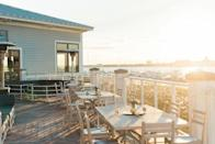 """<p><strong>What will we notice when we walk in?</strong> The elevation of this rooftop bar isn't anything to write home about as you're only a couple of stories up. However, its location on the tip of Patriots Point in the <a href=""""https://www.cntraveler.com/hotels/mount-pleasant/the-beach-club-at-charleston-harbor-resort-and-marina?mbid=synd_yahoo_rss"""" rel=""""nofollow noopener"""" target=""""_blank"""" data-ylk=""""slk:Charleston Harbor Resort"""" class=""""link rapid-noclick-resp"""">Charleston Harbor Resort</a> delivers some seriously alluring views, with the harbor, Ravenel Bridge, the Battery and panoramas all the way out to Fort Sumter all laid out for your approval. An aesthetic shaped by the reclaimed wood interiors parlays into a casual seaside chic, the open-plan design meaning that the bar area opens out onto that scenic terrace.</p> <p><strong>How's the crowd?</strong> The resort is a relatively luxurious waterfront hotel, and so there's a steady stream of vaguely affluent guests drinking here at any one time. Despite the upscale backdrop, though, there's a casual, vacation-friendly vibe and outside of occasional couples celebrating an anniversary at the attached restaurant, formality levels are low. It's a slightly more mature crowd than some of the downtown rooftop spots, with a civilized appreciation of the wonderful vistas preferred to noisy rounds of tequila shots.</p> <p><strong>How are the drinks?</strong> As an annex to the seafood restaurant next door, the bar has a suitably versatile and comprehensive wine list that draws heavily on bubbles and whites. A good number of French wines mix with Californians, the latter making up more of the reds. The cocktail menu is a solid selection of classics such as mojitos, margaritas and Moscow Mules, and the draft beer selection rotates regularly along with a couple of bottles for craft connoisseurs.</p> <p><strong>What do they have to eat?</strong> The bar serves a pared-down version of its wonderful seafood menu, and guests can"""