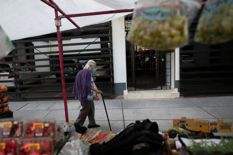 A  woman walks at the local street market after Mexico's government declared a health emergency on Monday and issued stricter rules aimed at containing the fast-spreading coronavirus disease (COVID-19), in Mexico City