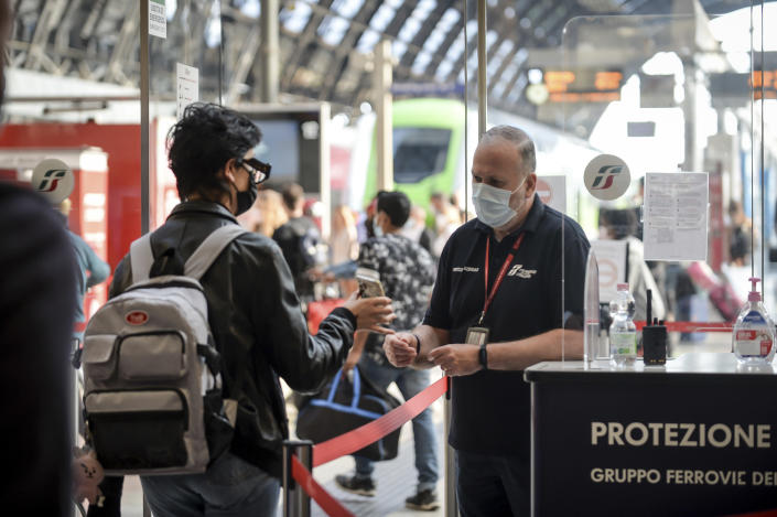 A passenger holds up his phone at a check point at Milan's Stazione Centrale train station, Italy, Wednesday, Sept. 1, 2021. The Italian government vowed to crack down on demonstrators threatening to block train tracks throughout the country on Wednesday as a rule requiring COVID-19 tests or vaccines takes effect for long-distance domestic public transport. (Claudio Furlan/LaPresse via AP)