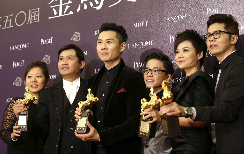 """Singaporean director Anthony Chen (3rd L) and cast members celebrate winning the Best Feature Film, the Best New Director, the Best Original Screenplay and the Best Supporting Actress (actress Yann Yann Yeo, 2nd R) for """"Ilo Ilo"""" at the 50th Golden Horse Film Awards in Taipei November 23, 2013. REUTERS/Patrick Lin (TAIWAN - Tags: ENTERTAINMENT)"""