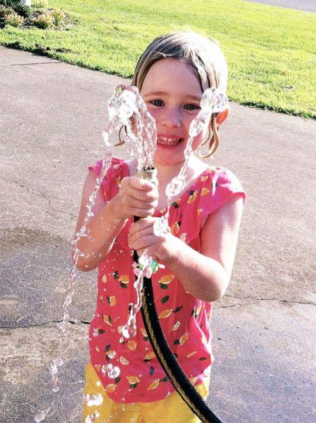 PHOTO: Sylvie plays with water from a hose in this undated family photo. (Courtesy Laura Sullivan-Beckers)