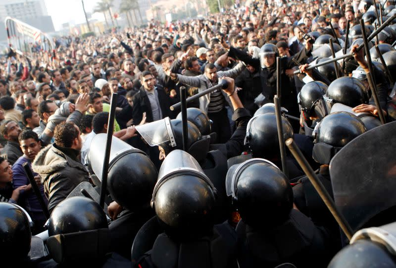 FILE PHOTO: Anti-government protesters demonstrate near riot police at Tahrir Square in downtown Cairo