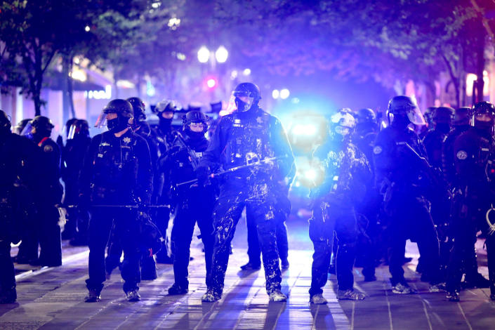 Portland Police and protesters clashed in a demonstration in downtown Portland, Wednesday, Aug. 12, 2020. Officers used tear gas to break up the crowd of several hundred people who gathered near the Mark O. Hatfield U.S. Courthouse, the neighboring Multnomah County Justice Center and a nearby police precinct station. (Sean Meagher/The Oregonian via AP)