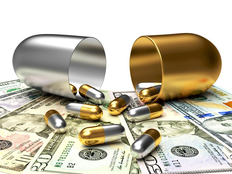 Gold and silver pills spill out onto a pile of money from a larger gold and silver pill capsule.