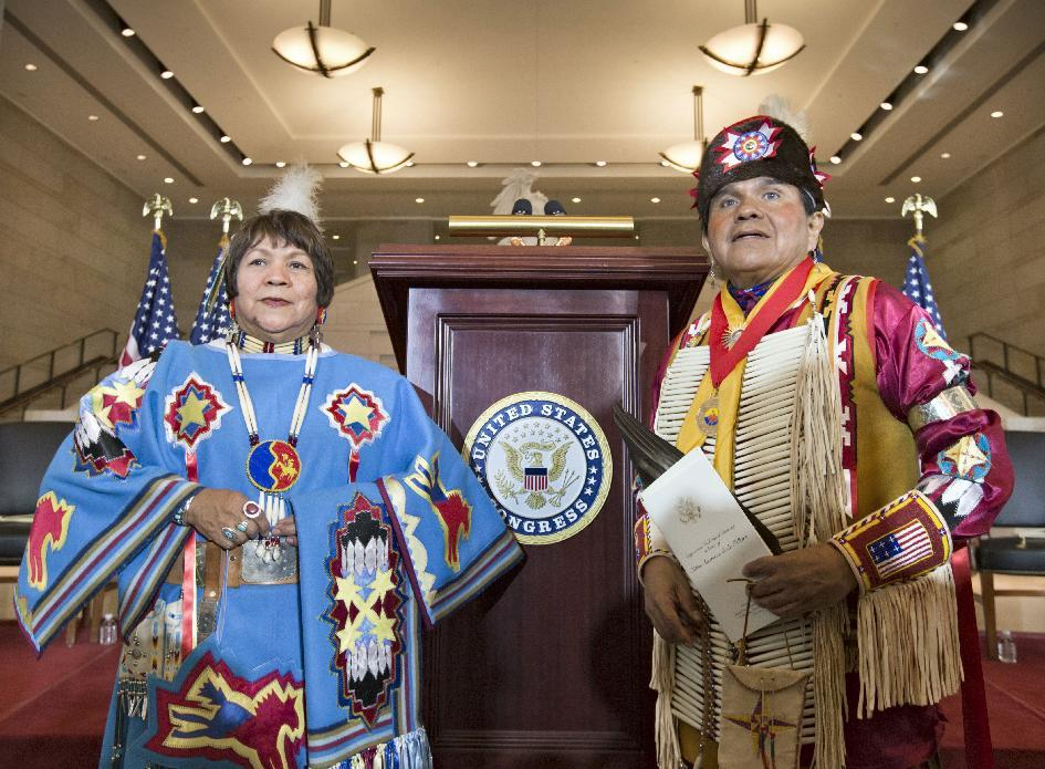 John Parker, right, and his sister LaNora Parker, left, members of Comanche Nation in Oklahoma, arrive for a Congressional Gold Medal ceremony on Capitol Hill in Washington, Wednesday, Nov. 20, 2013, honoring Native American code talkers who used their unique languages as a means of secret communication that enemy troops could not decipher during World War II,. Their father, Simmons Parker, was an Army code talker during World War II. (AP Photo/J. Scott Applewhite)