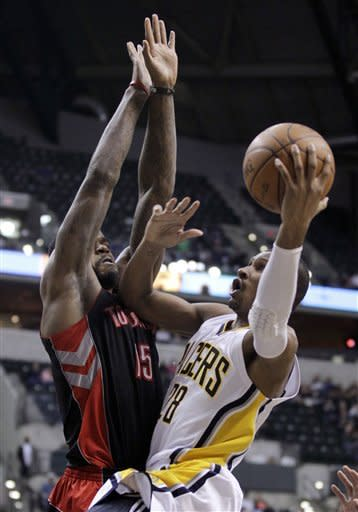 Indiana Pacers guard Leandro Barbosa, right, shoots under pressure from Toronto Raptors forward Amir Johnson in the second half of an NBA basketball game in Indianapolis, Monday, April 9, 2012. The Pacers defeated the Raptors 103-98. (AP Photo/Michael Conroy)