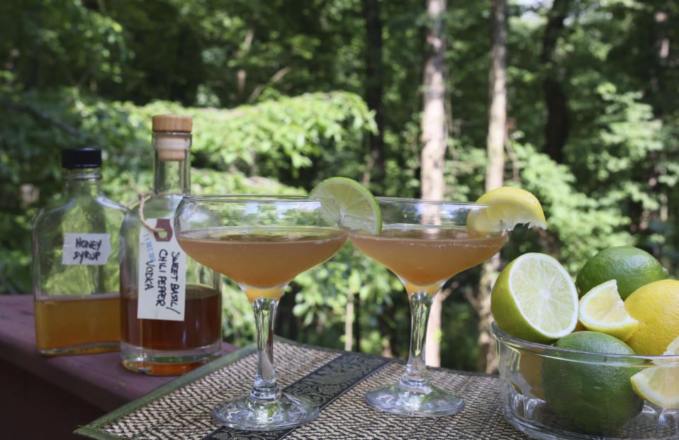 Cocktails containing alcohol and syrup infusions sit amid bottles and mixing accessories in Allison Park, Pa., on July 4, 2021. Alcohol and syrup infusions are growing in popularity and are relatively simple to incorporate into home bars. (AP Photo/Ted Anthony)