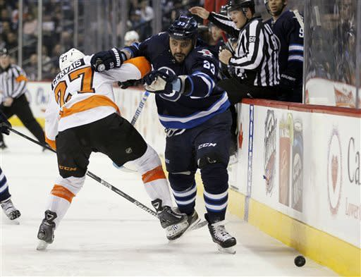 Winnipeg Jets defenseman Dustin Byfuglien, right, attempts to get around Philadelphia Flyers defenseman Bruno Gervais during the second period of an NHL hockey game in Winnipeg on Saturday, April 6, 2013. (AP Photo/The Canadian Press, John Woods)