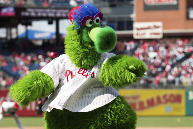In this April 5, 2018 photo, The Phillie Phanatic reacts prior to the first inning of a baseball game against the Miami Marlins in Philadelphia. Kathy McVay says she was at Monday, June 18, Phillies game when the team's mascot, the Phillie Phanatic, rolled out his hot dog launcher. McVay was sitting near home plate and all of a sudden she says a hot dog wrapped in duct tape struck her in the face. She left the game to get checked out at a hospital, and she says she has a small hematoma. The Phillies apologized to McVay Tuesday and the team has offered her tickets to any game. (AP Photo/Chris Szagola)