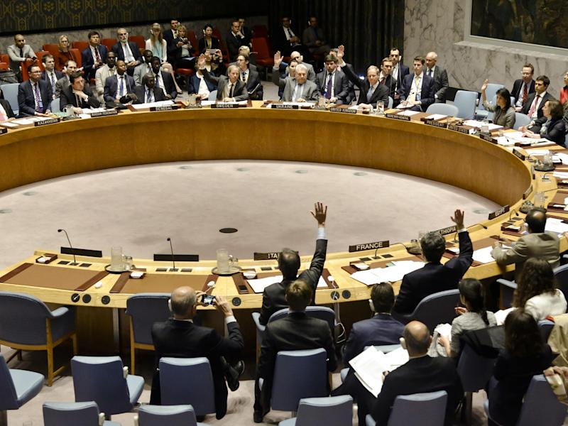 United Nations Security Council members show hands for a vote on a resolution condemning Syria's use of chemical weapons at UN headquarters: Bebeto Matthews/AP