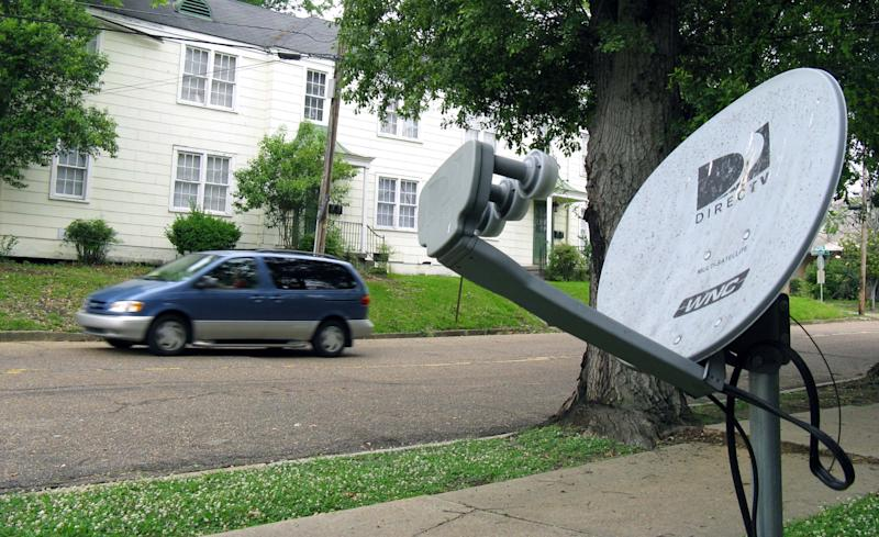 In this May 11, 2009 photo, a mini-van passes a DirecTV satellite dish in a residential area adjoining downtown Jackson, Miss. Tribune Broadcasting says there's been no settlement with DirecTV Inc. in their contract negotiations, which means DirecTV subscribers in 19 U.S. markets will lose access to certain programming, Saturday, March 31, 2012.  (AP Photo/Rogelio V. Solis)