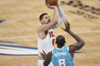 Chicago Bulls center Nikola Vucevic shoots over Charlotte Hornets center Bismack Biyombo during the second half of an NBA basketball game in Charlotte, N.C., Thursday, May 6, 2021. (AP Photo/Nell Redmond)