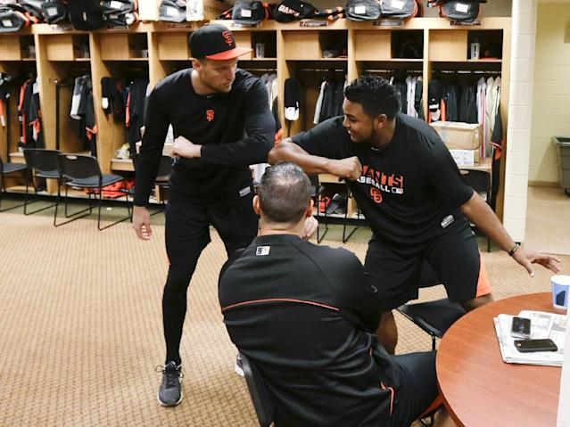San Francisco Giants outfielder Hunter Pence, left, greets pitcher Jean Machi, right, as catcher Guillermo Quiroz watches in the locker room at baseball spring training, Friday, Feb. 14, 2014, in Scottsdale, Ariz. Giants pitchers and catchers arrived Friday for physicals before beginning training Saturday