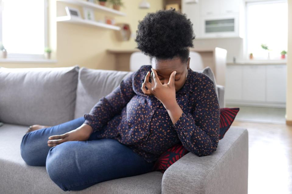 Young Black Woman Sitting on a Couch, Holding Her Head, Having a Strong Headache