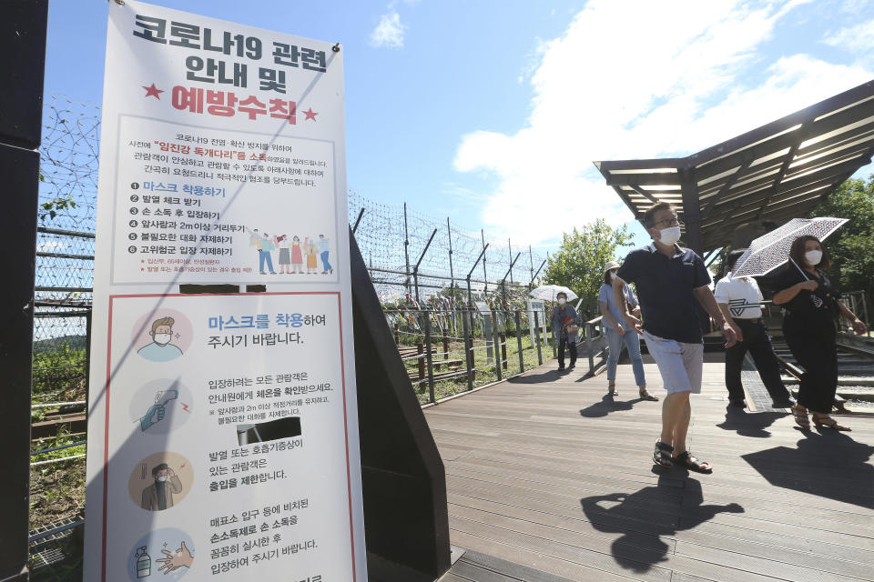 """People wearing face masks to help protect against the spread of the new coronavirus pass by a notice about precautions against the coronavirus disease at the Imjingak Pavilion in Paju, near the border with North Korea, Sunday, July 26, 2020. North Korean leader Kim Jong Un placed the city of Kaesong near the border with South Korea under total lockdown after a person was found with suspected COVID-19 symptoms, saying he believes """"the vicious virus"""" may have entered the country, state media reported Sunday. The banner reads """"The precautions against the coronavirus 19."""" (AP Photo/Ahn Young-joon)"""