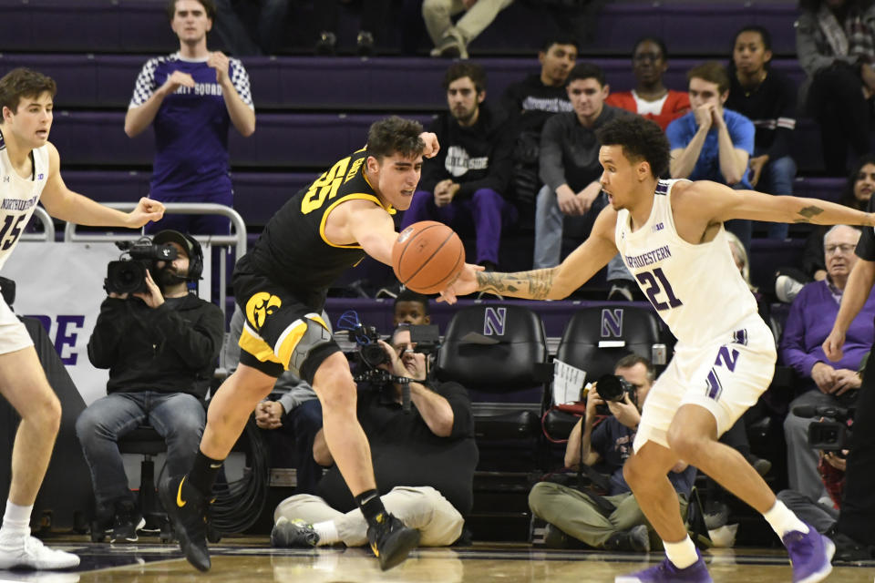 Iowa center Luka Garza (55) and Northwestern forward A.J. Turner (21) go for a loose ball during the second half of an NCAA college basketball game Tuesday, Jan. 14, 2020, in Evanston, Ill. (AP Photo/David Banks)